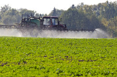 Traktorspray befruchten mit Insektenvertilgungsmittelherbizidchemikalien auf dem Landwirtschaftsgebiet Lizenzfreie Stockfotos