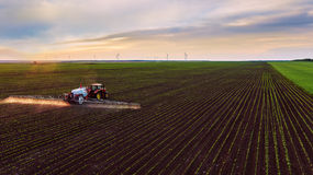Traktorsprühfeld am Frühling Stockfotografie