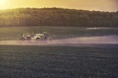 Traktorsprühsojabohnenfeld Stockfotos