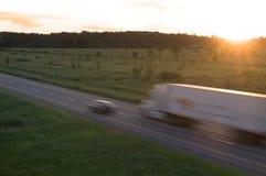 TraktorTrailor i rörelse på solnedgången Royaltyfria Foton