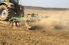 Traktorvåren behandlar jorden, innan den planterar Royaltyfri Fotografi