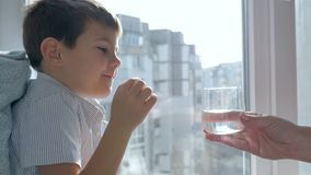 Traktowanie dziecko który bierze pigułkę i pije puszek wodę mineralną od przejrzystego szkła w pokoju zbiory wideo