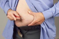 Traktowanie otyłość Gruby mężczyzna z strzykawką robi insulinowemu zastrzykowi on w domu Otyłości zagrożenie życia Cukrzycy trakt Zdjęcie Stock