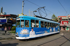 Tram in Antalya, Turkey. ANTALYA, TURKEY - AUGUST 18, 2014:  A tram traveling through the old town of Antalya with a poster for the city's mayor Menderes Türel Royalty Free Stock Images