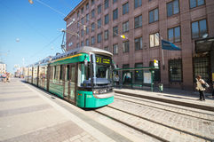 A tram is arriving to a station at the commercial district of Helsinki. Royalty Free Stock Image