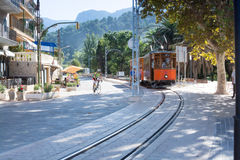 Tram and bike in Port de Soller. Street view in Port de Soller Mallorca with tram and crossing bicyclist and view towards the mountains, Soller, Mallorca Royalty Free Stock Photography