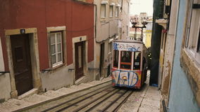 Tram car driving uphill through alley in Lisbon stock video