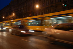 Tram and cars moving. Articulated yellow tram and cars fast moving at night in Budapest royalty free stock image