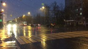 The tram and cars passing under a running snow. Red and white trams and cars passing on the road under a moving, falling snow, wet road, the lights illuminate stock footage