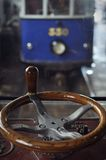 Tram control wheel. Frontal view of an old wooden tram control wheel with a blurred blue tram in the background behind glass Royalty Free Stock Photo