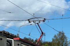 Tram current collector against the blue sky. Pantograph in working condition on the roof of an electric train stock images