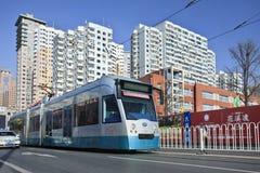 Tram de approche avec l'immeuble sur le fond, Dalian, Chine Image stock