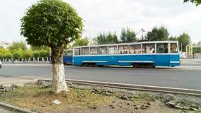 Tram de ville sur la rue de Temirtau, Kazakhstan Le vieux tram sur la route est sur une section droite de la route le long Photographie stock