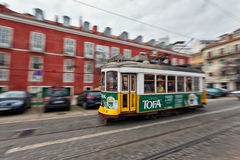 Tram, die durch Lissabon-Straßen überschreitet Stockbild