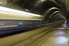 A tram disappearing into a tunnel Stock Photo