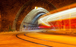 Tram drives in the tunnel at night Stock Photos