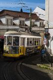 The 28 Tram Electrico 28 in a narrow street in the Alfama neighborhood, in the city of Lisbon. Lisbon, Portugal - February 17, 2019: The 28 Tram Electrico 28 in stock images