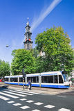 Tram with famous Wester Tower on background, Amsterdam, Netherlands. Stock Images