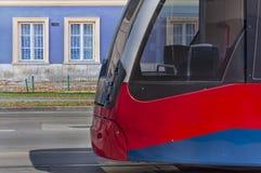 Tram ferroviaire électronique public moderne rouge sur la fin de rue Image libre de droits