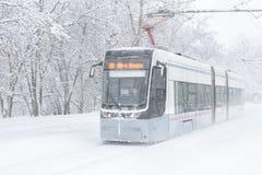 Tram geht entlang die Straße während des Schneesturmes am Winter in Moskau Lizenzfreies Stockbild