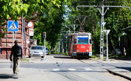 Tram goes through a green alley in Tomsk city. TOMSK, RUSSIA - JUNE 4, 2016: Tram goes through a green alley in Tomsk city Royalty Free Stock Photography