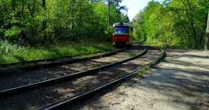 The tram rides on rails in the middle of the forest. The tram goes on rails among the green forest. Interesting places in city Kiev stock video
