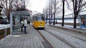Tram jaune arrivant à un arrêt avec des passagers image stock