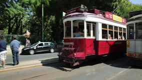 Tram 28 Lisbon. Lisbon, Portugal - August 27, 2017: historic Tram 28 and red Hills tramcar tour at Estrela Basilica terminal and people waiting to climb the icon stock footage