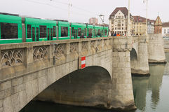 Tram passes by the bridge over Rhine river in Basel, Switzerland. Royalty Free Stock Images