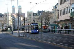 A blue tram in downtown Munich on a bright winter`s morning. A tram passesthrough Munich city centre in January as workers` unions threaten strikes across the Royalty Free Stock Image