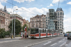 A tram passing through the Dancing House in Czech Republic Royalty Free Stock Photos