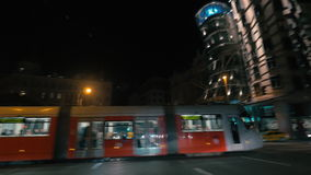 Tram passing by Dancing House at night, Prague. PRAGUE, CZECH REPUBLIC - APRIL 28, 2016: City tram moving along the night street and passing by Dancing House stock footage