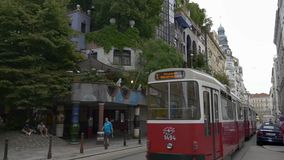 Tram is passing Hundertwasser house. VIENNA, AUSTRIA - AUGUST 2016: Lowengasse street. Classical style buildings next to contemporary Hundertwasserhaus. Old stock video