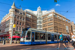 Tram passing tourists on Rembrandtplein Amsterdam Stock Images