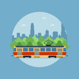 Tram. Picture of a tram in front of the trees and big sity silhouette Stock Photo