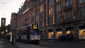 Tram pulls up to stop on Damrak, Amsterdam. Tram pulls up to stop on Damrak in Central Amsterdam. The Bijenkorf department store is in the background. Taken at stock footage