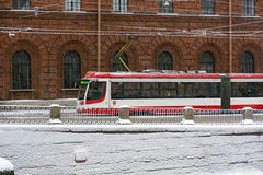 Tram rides along brick building, snowing Stock Photography