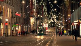 Tram rides down the street in the city center. HELSINKI, FINLAND - DECEMBER 27, 2015: Tram rides down the street in the city center decorated for Christmas on stock footage