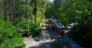 Tram stop in the green forest. Kiev. The tram rides on rails in the middle of the forest, stop, people. Kiev, Ukraine stock footage