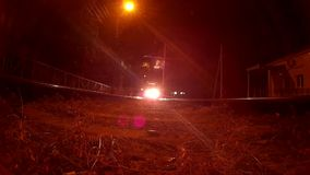 Tram rides the rails and passes over the camera at night,. View from below stock video footage