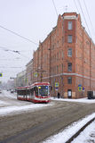 Tram rides on road, street, city, old buildings, rails, wires, s Stock Photos