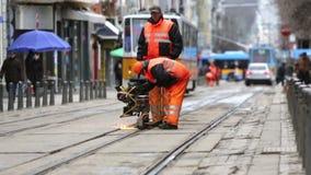 Tram road workers repair repairing. Sofia, Bulgaria - April 7, 2015: Tram road workers are repairing the tram tracks on the tram road stock video