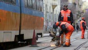 Tram road workers repair repairing. Sofia, Bulgaria - April 7, 2015: Tram road workers are repairing the tram tracks on the tram road stock video footage