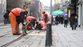 Tram road workers repair repairing. Sofia, Bulgaria - April 7, 2015: Tram road workers are repairing the tram tracks on the tram road stock footage