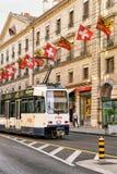 Tram in Rue Corraterie Street met Zwitserse vlaggen Genève Zwitser stock fotografie