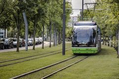 The tram runs through the city center on tracks surrounded by grass.
