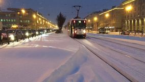 The tram on snow-covered rails approaching the bus stop stock video