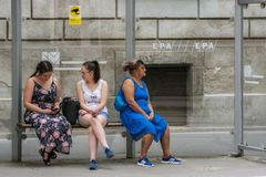 At the tram stop. Budapest, Hungary, July 4: Two young girls and a woman are waiting for the tram, sitting at a stop on one of the streets in Budapest on July 4 royalty free stock photos