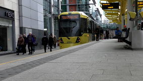 Tram stop in Manchester city. MANCHESTER, ENGLAND, UK - FEBRUARY, 2017: In the city centre center light rail Metrolink yellow colour tram arrives at the stop stock footage