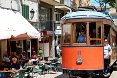 The tram is on street of Soller town. MALLORCA, SPAIN - JUNE 2: The tram is on street of Soller town and tourists are in outdoor restaurant on June 2, 2015 in Stock Images